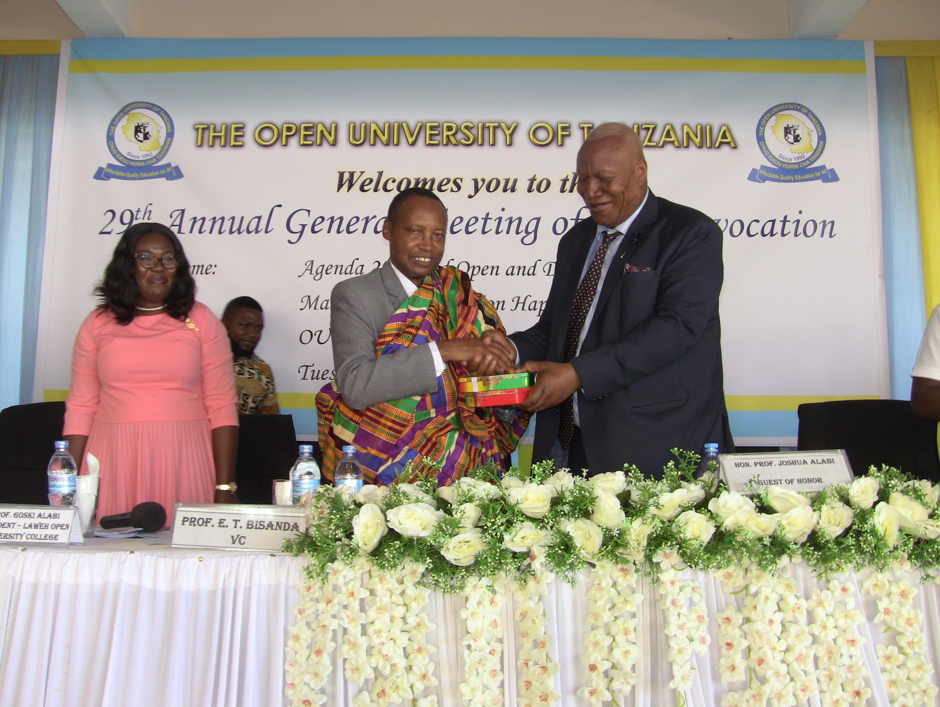 The Vice Chancellor of the Open University of Tanzania Prof. Elifas Bisanda, receives a gift from the President of Laweh Open University of Accra, Ghana Prof. Joshua Alabi during the 29th Annual General Meeting Of the Convocation