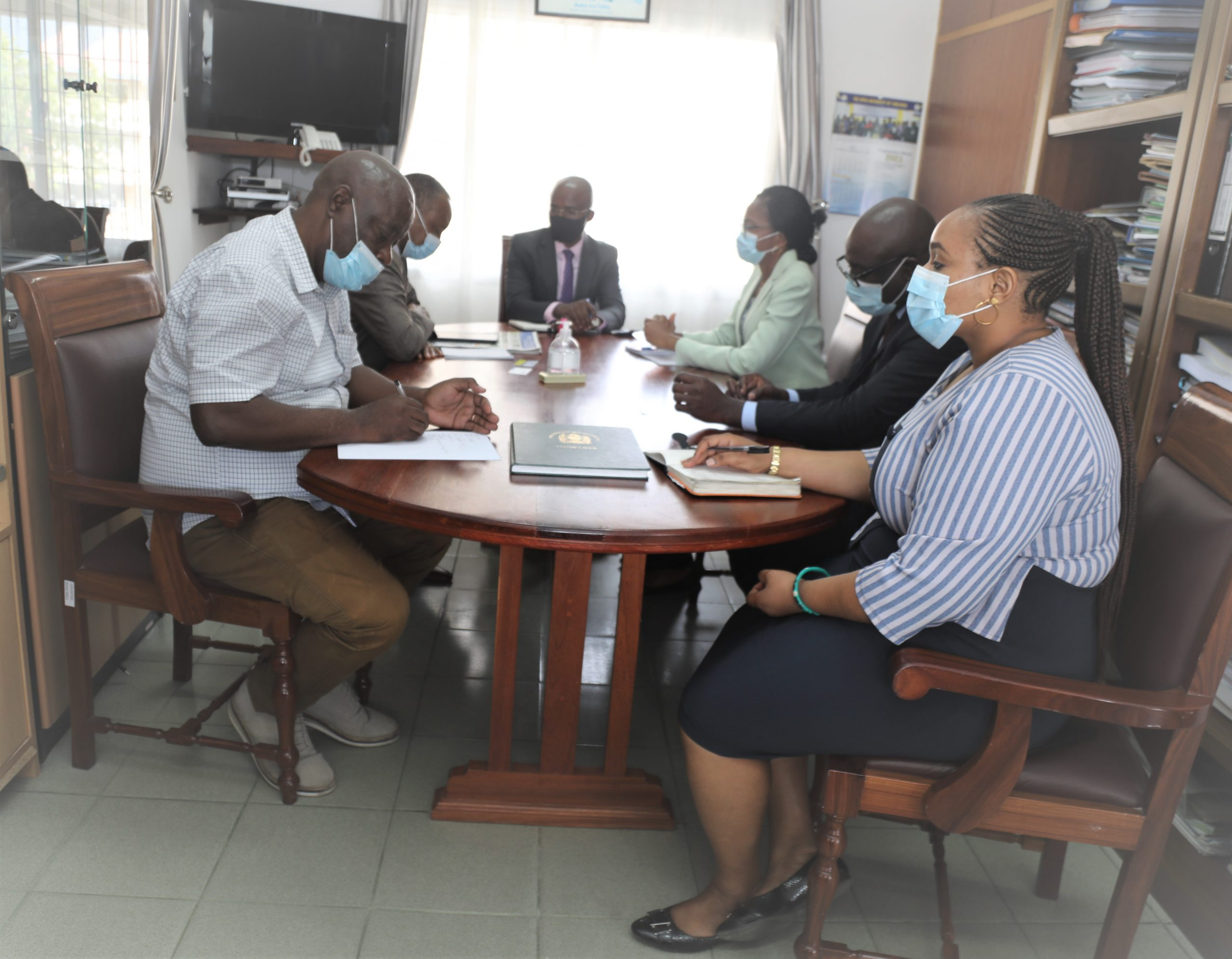 The Vice Chancellor of the Open University of Tanzania (OUT), Prof. Elifas Bisanda, embraces members of the NMB Bank PLC